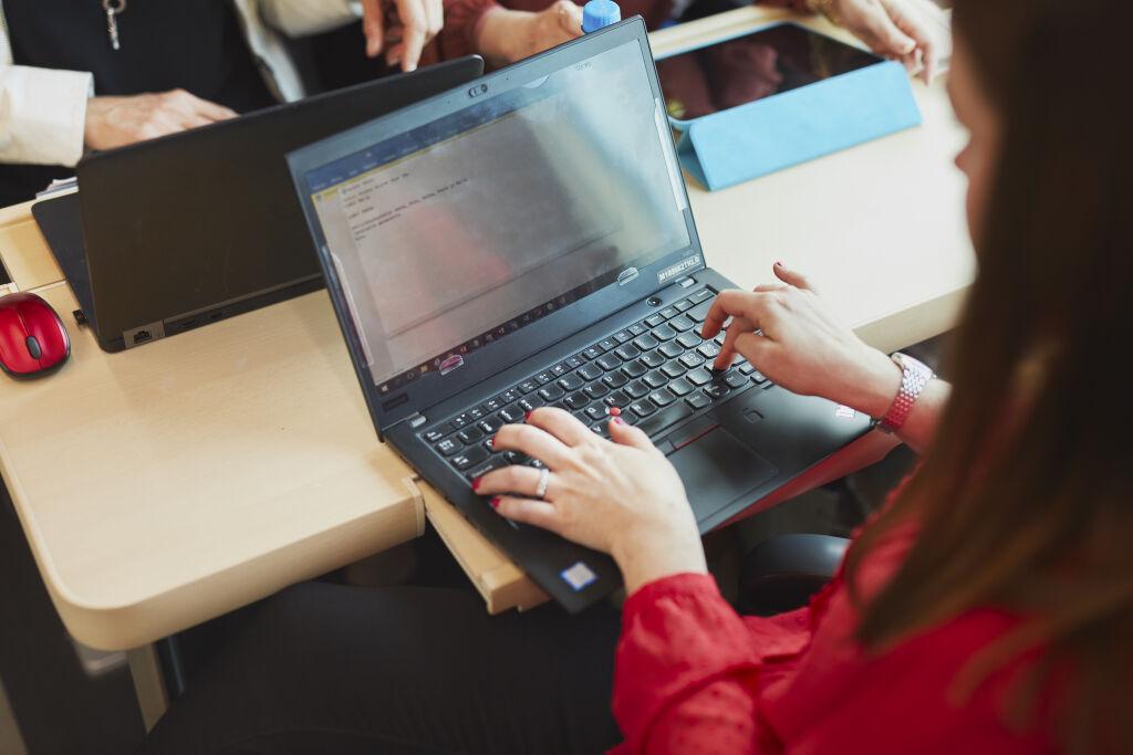 Nainen junassa tietokoneen kanssa