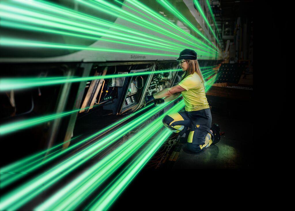 Asentaja huoltaa junaa varikolla. Päällä kulkee vihreitä valojuovia.
