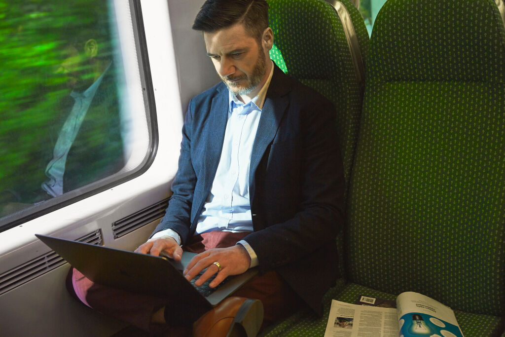 Man working on computer on train